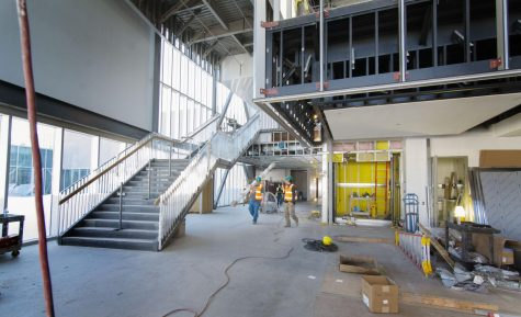 Construction workers move many planks to the second story of the new Student Union building.