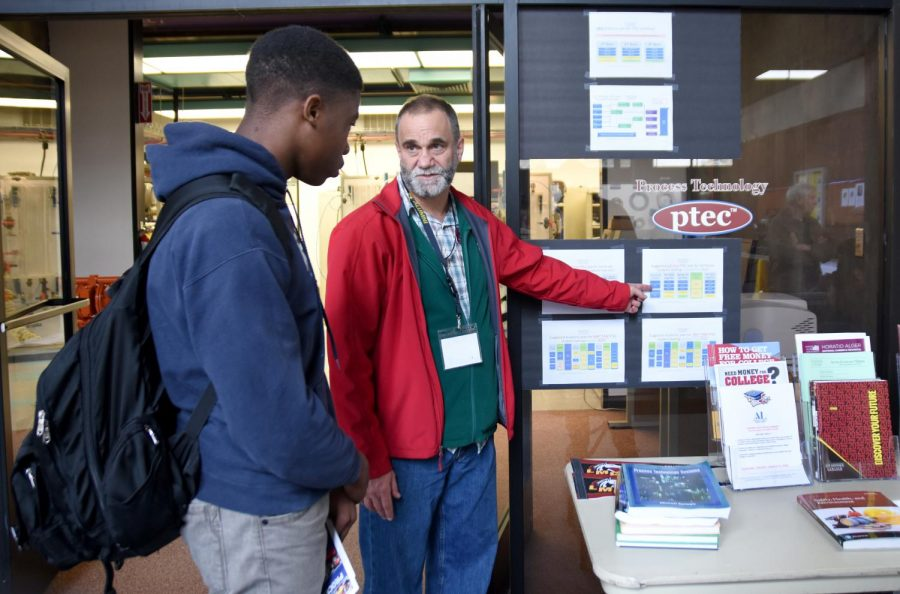 Michael Kean explains to student Chisom Iwunze about the PTEC classes during the PTEC Open House, Dec. 10.