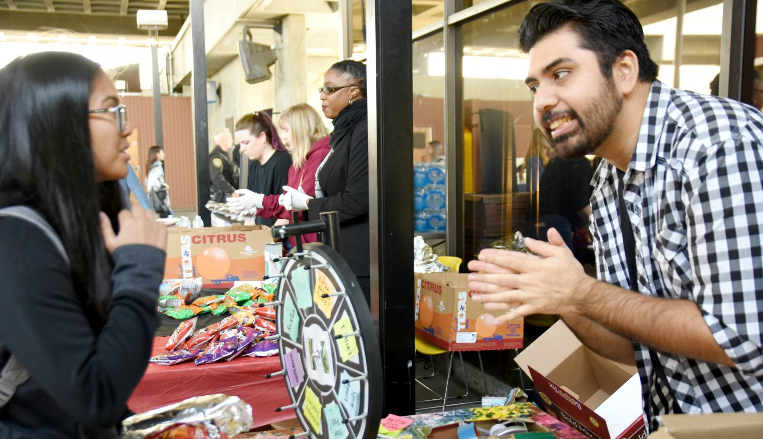 A student interacts with Fabian Ortega (right) before spinning the wheel of prizes during Mustang Day.