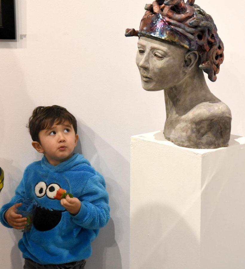 "Miles Yoshimoto gazes at mom Natalie Yoshimoto's sculpture ""Medusa"" at the LMC Student Art Show."