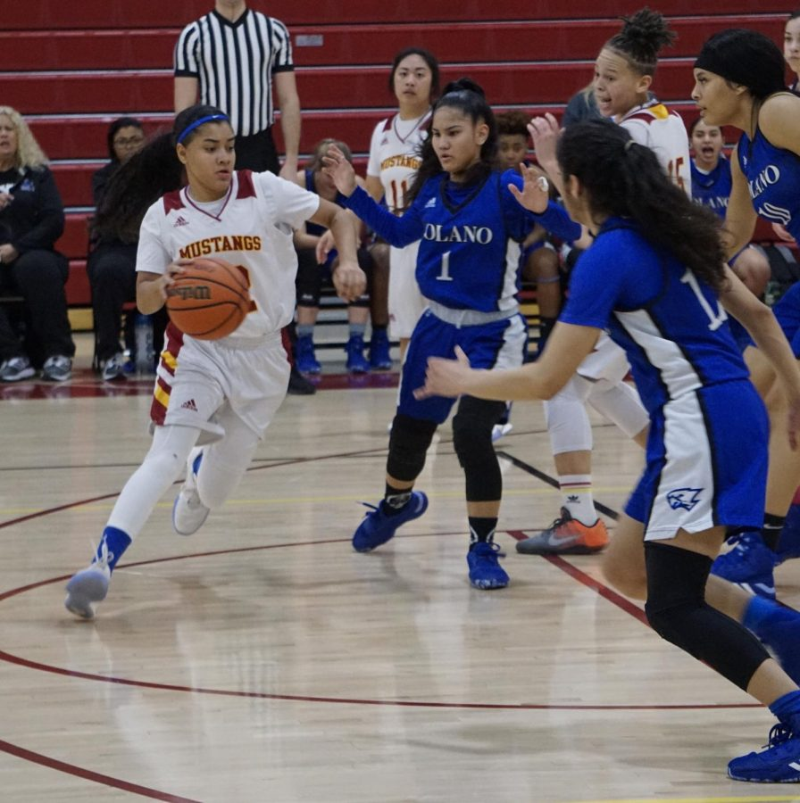 Jeannette Luna, No. 12, attempts to dribble through the Solano College Falcons in an attempt to score for the Mustangs during a women's basketball game at Los Medanos College in Pittsburg, Calif. on Jan. 31, 2020.