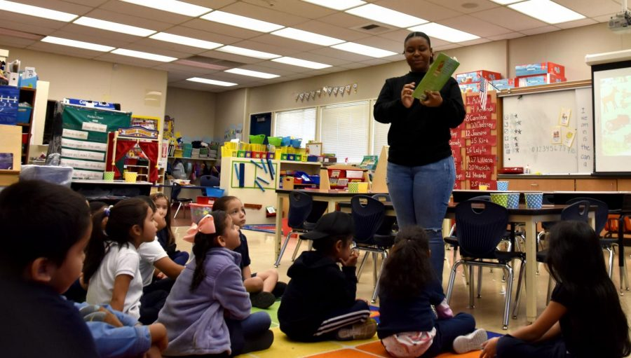 Melan George, an LMC student in the Umoja program, reads to Foothill Elementary School children.