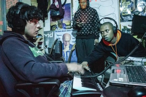 Above, AG Club crafts a song in their garage studio. Seated left is Loui, who uses a digital keyboard to mix together the instrumental. Seated right, reaching over, is Babyboy, who asks Loui how certain affects can be added to make his vocals more interesting. Behind them is Jody Fontaine, mulling over lyrics he wrote.