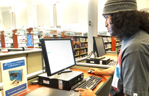 Robert McCune uses Library computers to print out his homework which students cannot do at the moment due to the closure. Photo taken in 2013.