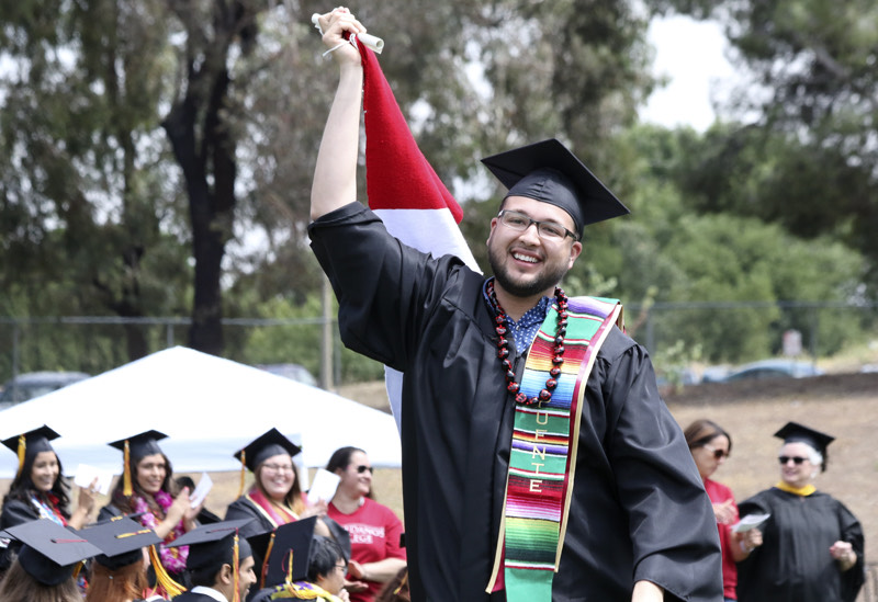 Jesus Briseno proudly waves a Mexican flag as he walks up to the stage at graduation. Photo taken in 2017.