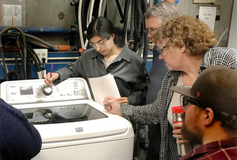 Students Marlene Lopez (left), Steve Lowery and Instructor Debra Winckler go over how to fix a washer. Photo taken in 2019