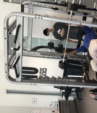 LMC students Jahleel Lloyd and Migel Norwood use the weight-lifting equipment inside the Fitness Center.