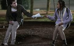 Ben Platt as Evan Hansen and Amandla Stenberg as  Alana Beck sitting together on a swing set.