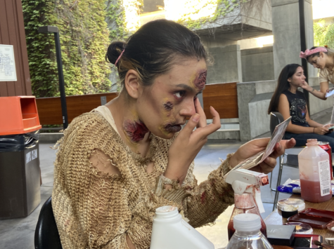 """Makeup artist and actor Nyla Rahimi applies zombie makeup during the filming of """"Death and Silence,"""" at LMC on Sunday, Sept. 26."""